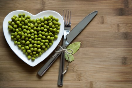 Heart-shaped plate with green peas